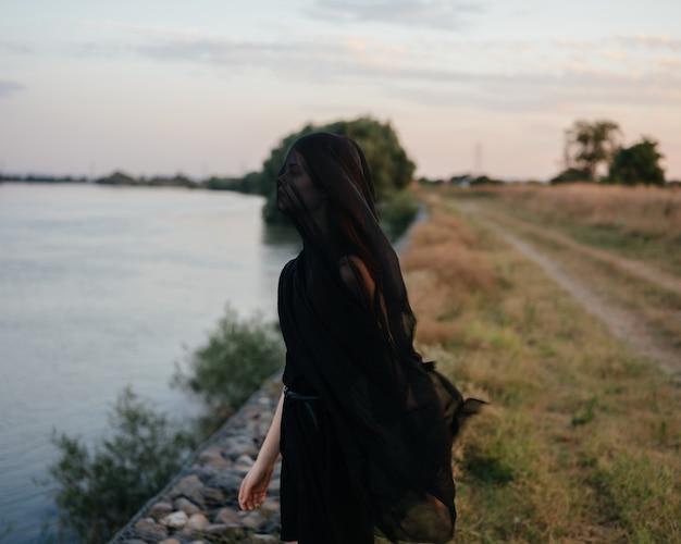 Jolie femme tissu noir posant nature paysage à pied
