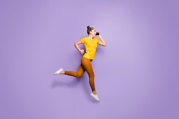 Jolie femme avec topknots posant contre le mur violet