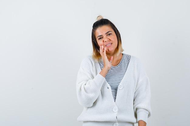 Jolie femme touchant la joue avec les doigts en t-shirt, cardigan et ayant honte.