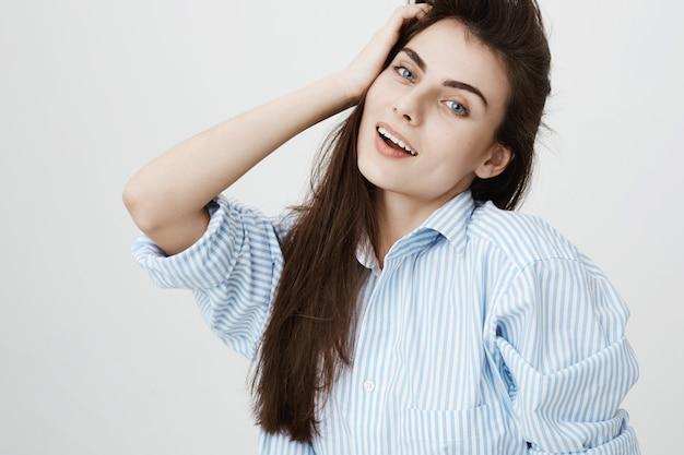 Jolie femme touchng cheveux et souriant