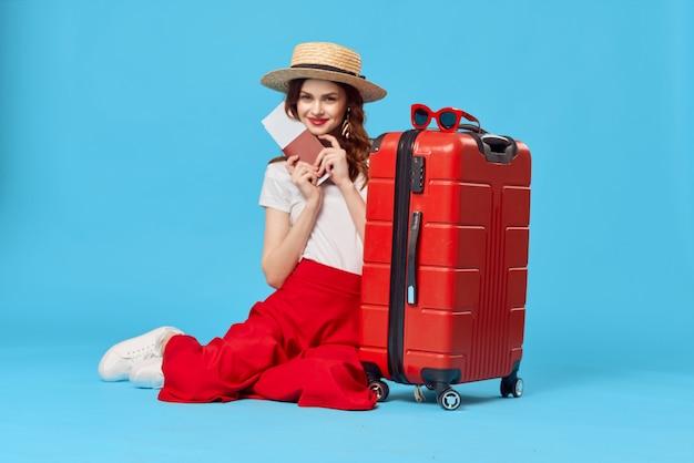Jolie femme touriste portant chapeau valise rouge vacances fond bleu