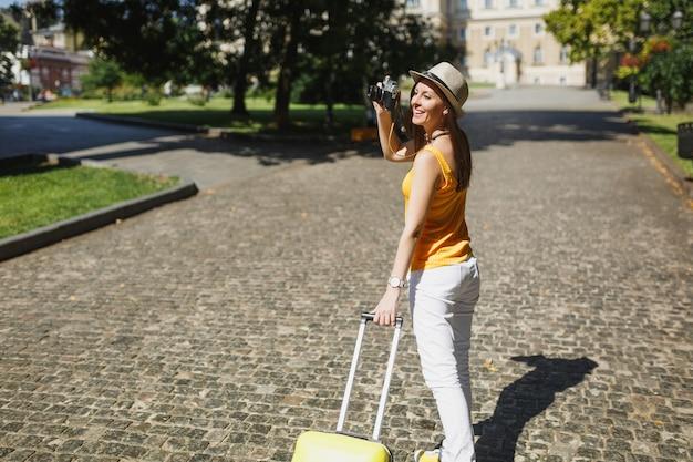 Jolie femme touristique en vêtements jaunes avec valise prendre des photos sur un appareil photo vintage rétro marchant dans la ville en plein air. fille voyageant à l'étranger le week-end. mode de vie de voyage touristique.