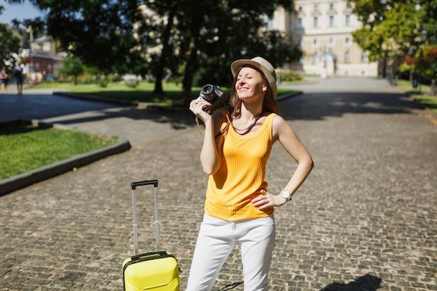 Jolie femme touristique voyageuse aux yeux fermés dans des vêtements décontractés jaunes, chapeau avec valise tenant un appareil photo vintage rétro en plein air. fille voyageant à l'étranger en week-end. mode de vie de voyage touristique.