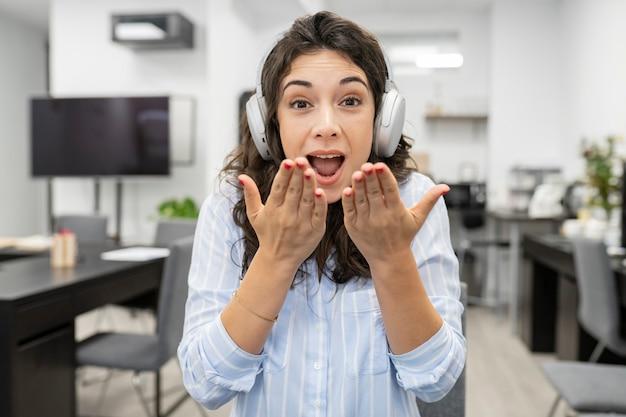 Jolie femme travaillant au bureau, avec des écouteurs fait un appel vidéo en soufflant des baisers
