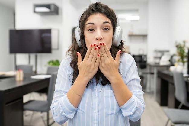 Jolie femme travaillant au bureau, portant des écouteurs fait un appel vidéo