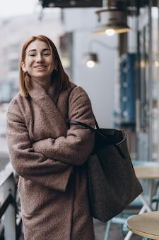 Jolie femme en trench-coat sur la rue de la ville