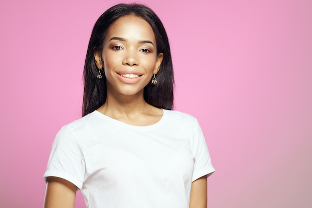 Jolie femme en tshirt blanc apparence africaine boucles d'oreilles cosmétiques fond rose