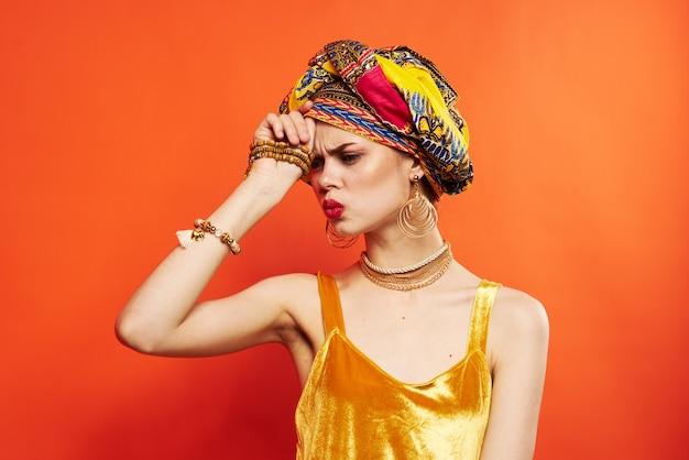 Jolie femme en turban multicolore look attrayant modèle de studio de bijoux
