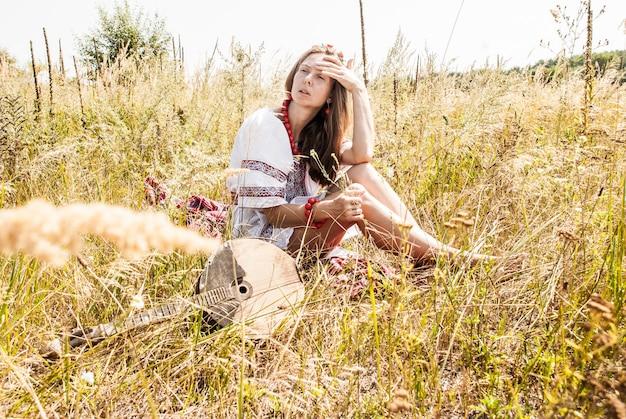 Jolie femme ukrainienne vêtue de vêtements brodés dans le champ