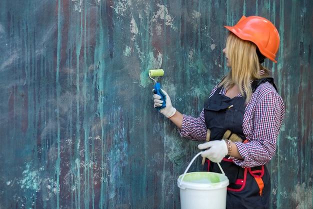 Jolie femme en uniforme et casque tenant la peinture et le rouleau s'apprête à rénover la maison. ouvrier du batiment.