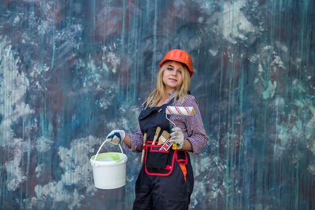 Jolie femme en uniforme et casque tenant de la peinture et un rouleau se préparant à rénover la maison. ouvrier du batiment.