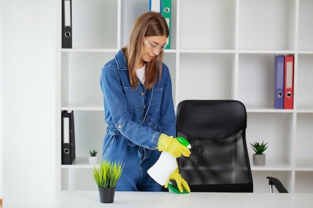Jolie femme en uniforme avec des fournitures de nettoyage au bureau.