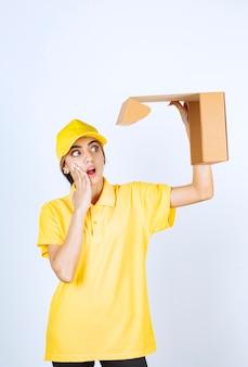Une jolie femme en uniforme jaune tenant une boîte de papier kraft vierge marron ouverte.