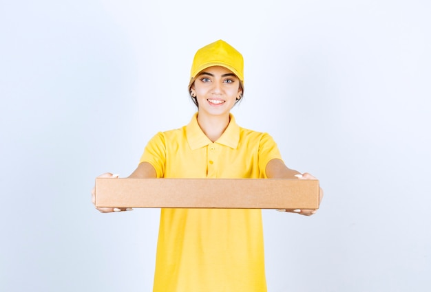 Une jolie femme en uniforme jaune tenant une boîte de papier kraft vierge marron.
