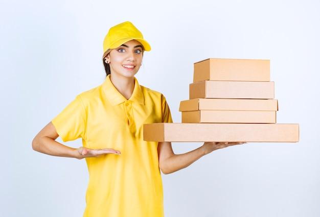 Une jolie femme en uniforme jaune tenant des boîtes de papier kraft vierge marron.