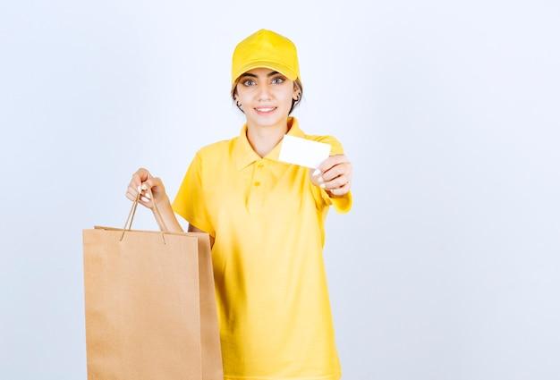 Une jolie femme en uniforme jaune tenant un sac en papier craft vierge marron.