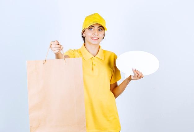 Une jolie femme en uniforme jaune tenant un sac en papier kraft vierge marron et une bulle de dialogue vierge.