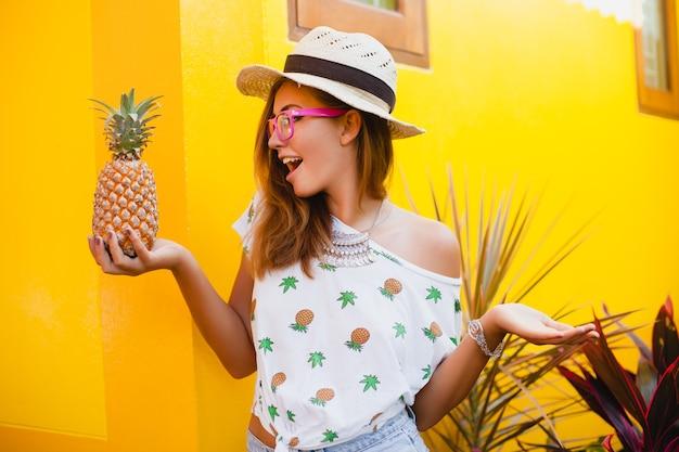 Jolie femme en vacances d'été avec l'expression du visage drôle souriant émotionnel portant chapeau de paille assis pieds nus surpris