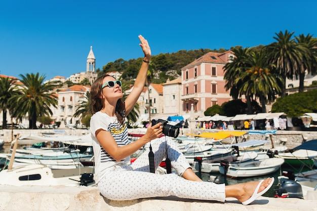 Jolie femme en vacances en europe au bord de la mer lors d'une croisière à prendre des photos à la caméra