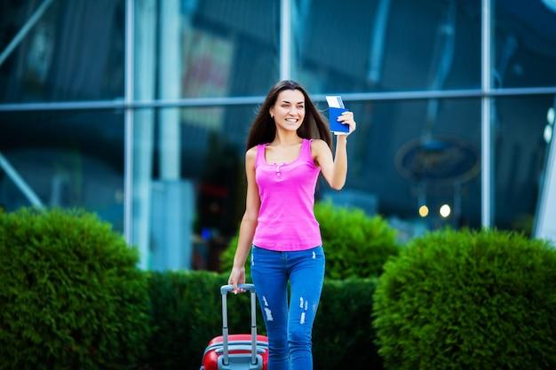 Jolie femme avec une valise près de l'aéroport en voyage