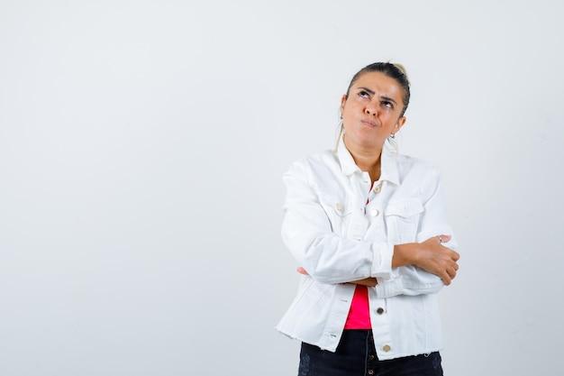 Jolie femme en veste blanche gardant les bras croisés, levant les yeux et regardant réfléchie, vue de face.