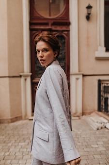Jolie femme en veste veste surdimensionnée se promenant dans la ville. belle femme aux cheveux noirs en tailleur-pantalon gris se penche sur la caméra et se déplace à l'extérieur