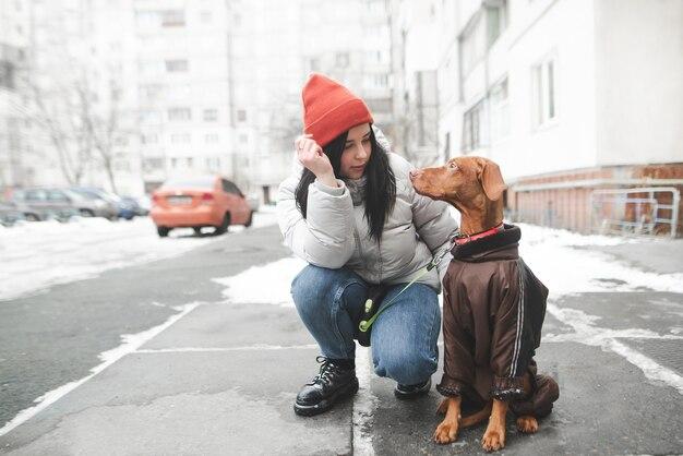 Jolie femme en vêtements chauds assis dans la rue avec un chien