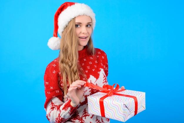 Jolie femme en vêtements de noël ouvrant une boîte cadeau.