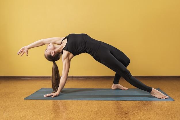 Une jolie femme en vêtements de sport noirs pratiquant le yoga effectue un exercice de kamatkarasana dans une pièce près du mur