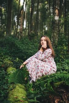 Une jolie femme vêtue d'une robe à fleurs est assise avec un bouquet de fougères dans la forêt.