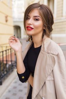 Jolie femme vêtue d'une robe noire et trench beige avec une coiffure élégante et des lèvres rouges dans la rue