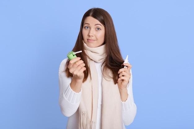Jolie femme vêtue d'une tenue décontractée avec une expression faciale étonnée, tenant un remède dans les mains