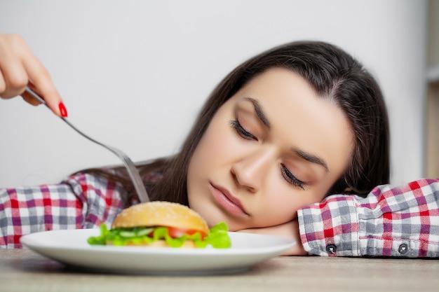 Jolie femme veut manger un hamburger nocif