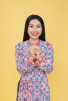 Jolie femme vietnamienne en costume traditionnel, isolée sur fond jaune