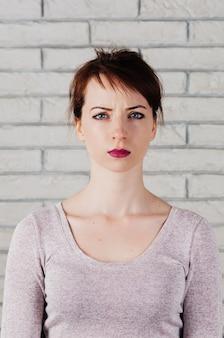 Une jolie femme avec un visage fronçant les sourcils, de grands yeux bleus, des lèvres roses pleines, un mur de briques blanches