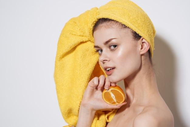 Jolie femme vous serviette jaune sur la tête oranges agrumes peau propre fond clair.