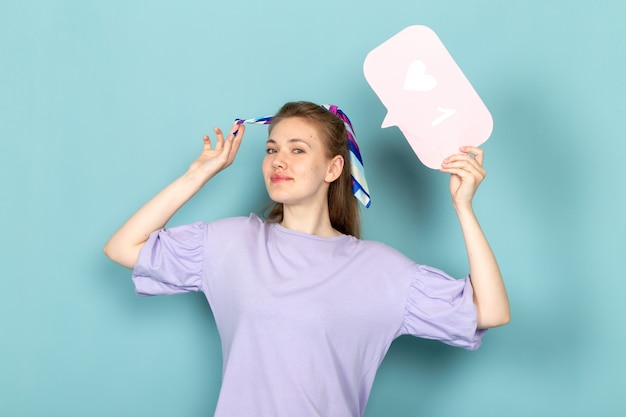 Une jolie femme vue de face en robe-chemise bleue tenant une pancarte blanche et souriant sur bleu