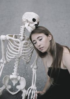 Jolie femme avec des yeux proches assis sur l'asphalte avec un squelette décoratif d'homme