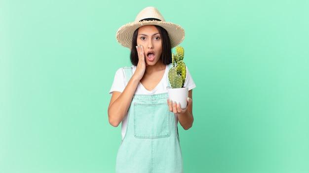 Jolie fermière se sentant choquée et effrayée et tenant un cactus