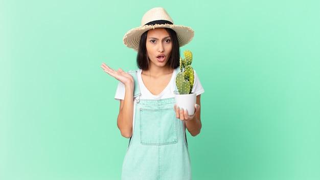 Jolie fermière semblant surprise et choquée, avec la mâchoire tombée tenant un objet et tenant un cactus