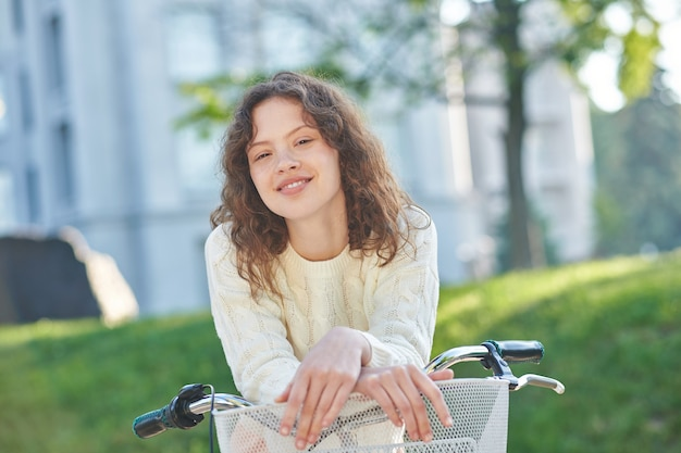 Une jolie fgirl sur un vélo se sentant bien et souriante