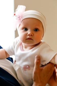 Jolie fille de 6 mois aux yeux bleus heureux en bandage blanc sur les mains de son père