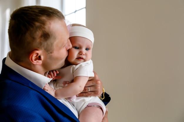 Jolie fille de 6 mois aux yeux bleus heureux dans un bandage blanc sur les mains du père de l'homme