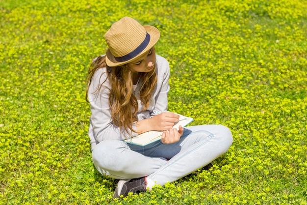 Jolie fille adolescente écrit des notes sur un bloc-notes sur un pré vert.