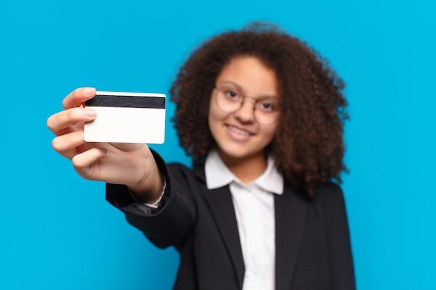 Jolie fille d'affaires adolescente afro avec une carte de crédit. concept d'achat en ligne