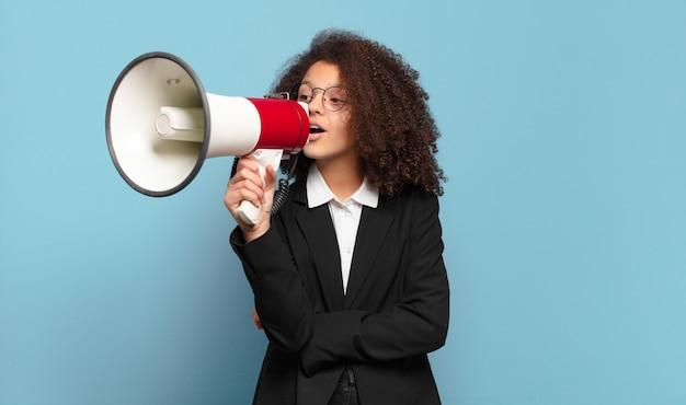 Jolie fille d'affaires adolescente afro avec un mégaphone