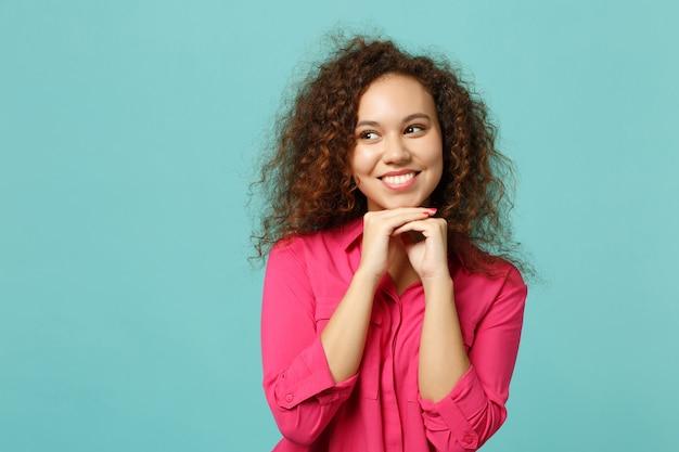 Jolie fille africaine souriante dans des vêtements décontractés regardant de côté, mettez la main sur le menton isolé sur fond bleu turquoise en studio. les gens émotions sincères, concept de style de vie. maquette de l'espace de copie.