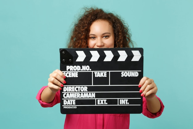 Jolie fille africaine en vêtements décontractés couvrant le visage avec un film noir classique faisant un clap isolé sur fond bleu turquoise. les gens émotions sincères, concept de style de vie. maquette de l'espace de copie.