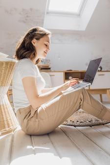 Jolie fille africanamerican utilise un ordinateur portable et sourit assis sur le sol