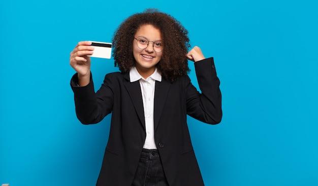 Jolie fille afro adolescente avec une carte de crédit. concept de magasinage en ligne